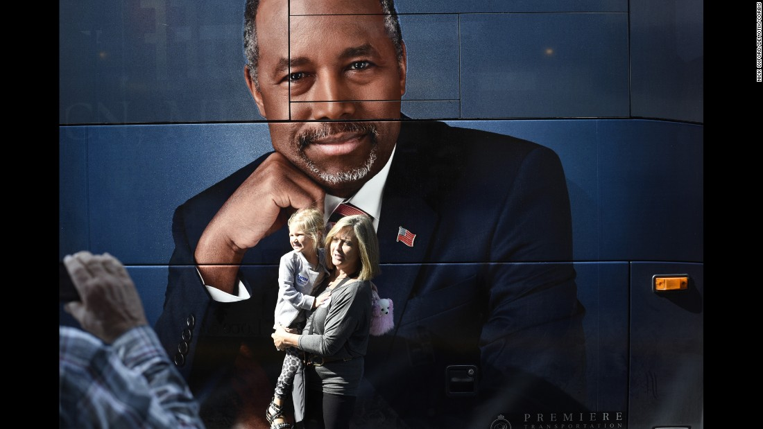 Supporters of Republican presidential candidate Ben Carson stand in front his tour bus at a book signing in Edmond, Oklahoma, on Wednesday, October 21.