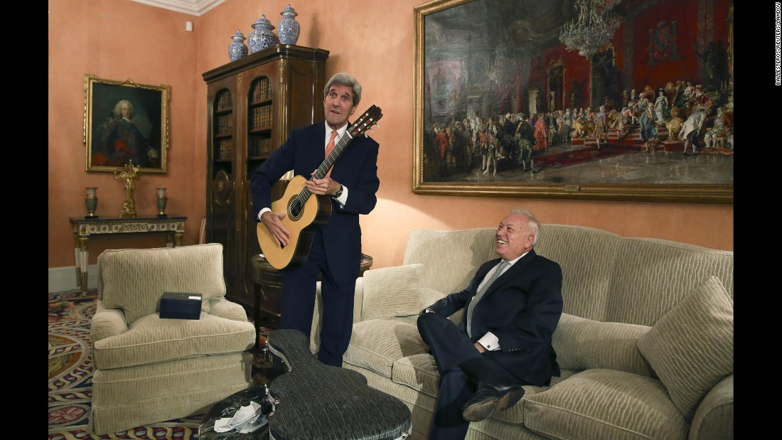 U.S. Secretary of State John Kerry poses with a guitar that was given to him by Spanish Foreign Minister Jose Manuel Garcia-Margallo during a meeting in Madrid on Sunday, October 18.