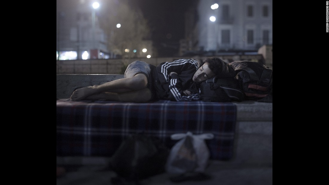 "Abdul Karim Addo, 17, sleeps in Omonoia Square in Athens, Greece. He has no money left. He bought a ferry ticket to Athens with his last euros. Now he spends the night where hundreds of refugees are arriving every day. He is able to borrow a telephone and call home to his mother in Syria, but he is not able to tell her how bad things are. ""She cries and is scared for my sake, and I don't want to worry her more,"" he said. He unfolds his blanket in the middle of the square and curls up in the fetal position. ""I dream of two things: to sleep in a bed again and to hug my younger sister."""
