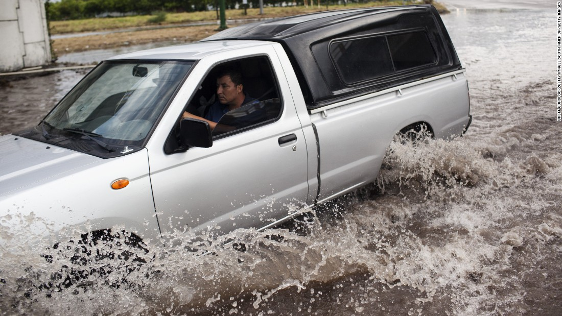 A truck driver braves a flooded street leading into Tecomán, Colima state.