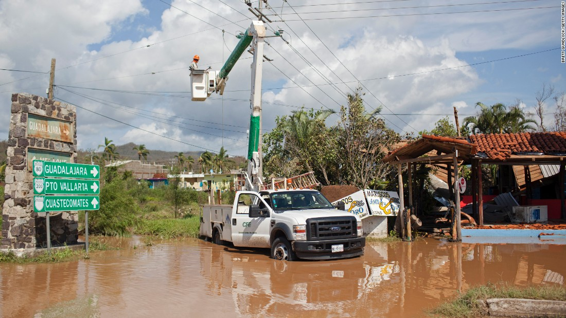 Men work to restore downed power lines on October 24 in Melaque.