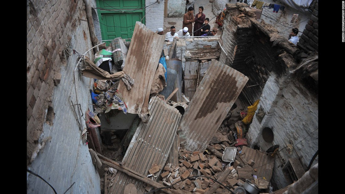 People look at a damaged house in Peshawar.
