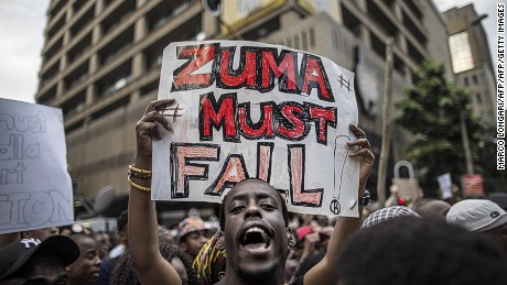 "A student holds a placard reading 'A placard with ""Zuma must fall"" outside the Luthuli House, the ANC headquarters, on October 22, 2015, in Johannesburg, during a demonstration of thousands of students against university fee hikes."