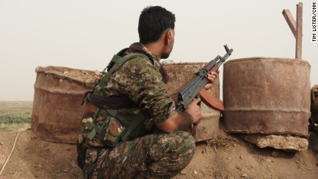 A soldier with the Kurdish YPG looks out over the front line in the fight against ISIS
