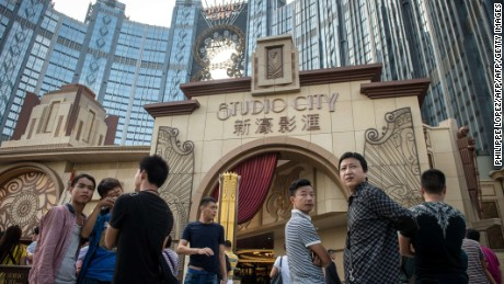 People stand outside the Studio City casino ahead of its opening in Macau on October 27, 2015. Casino operator Melco Crown was to open its latest resort Studio City as the city scrambles to diversify from gambling to the mass-market amid falling revenues.