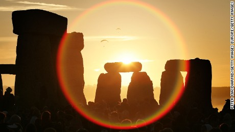 People watch the midsummer sun as it rises over Stonehenge