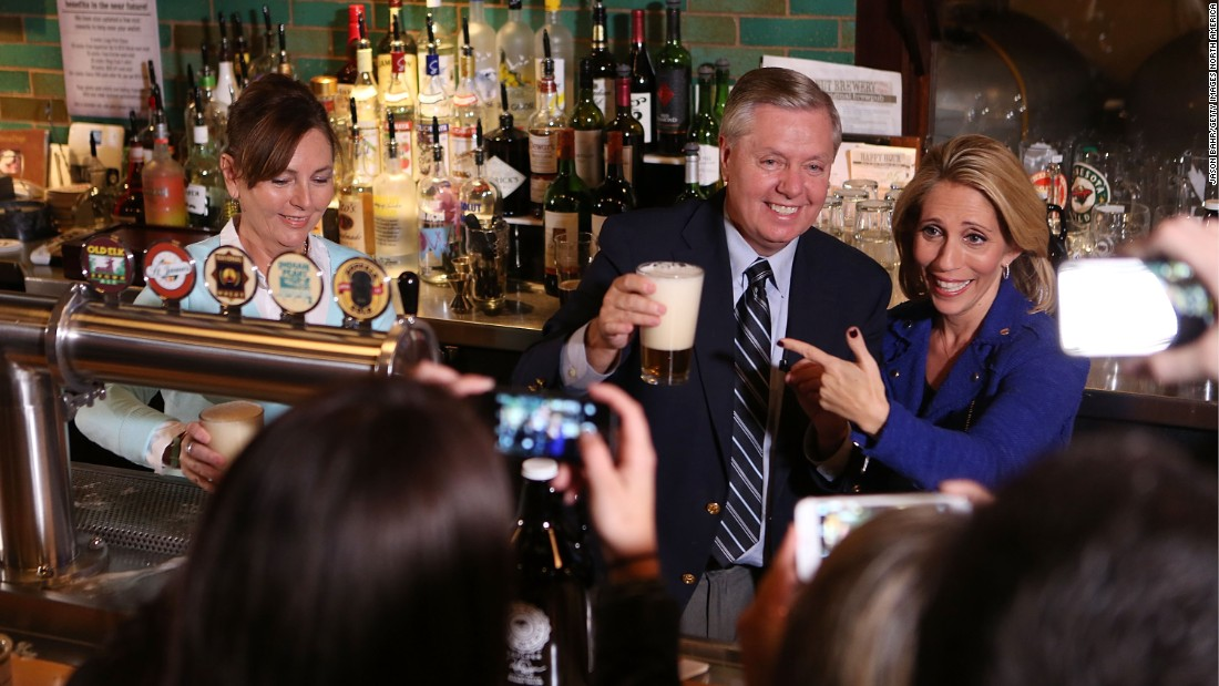 CNN's Dana Bash and U.S. Sen. Lindsey Graham serve beer to guests in Boulder, Colorado, prior to CNN's Politics on Tap event in October.