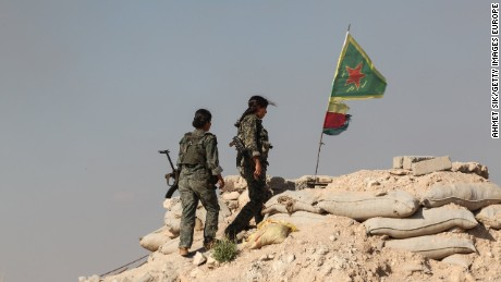 Female YPG fighters walk to a checkpoint on the outskirts of the destroyed Syrian town of Kobane.