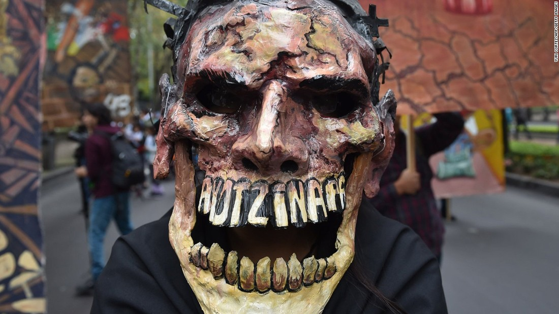 "In September one protester's mask particularly caught the media's attention: a deathly face whose teeth spelled ""Ayotzinapa"", the city in Guerrero state from which the students originate.<br /><br /><br />"