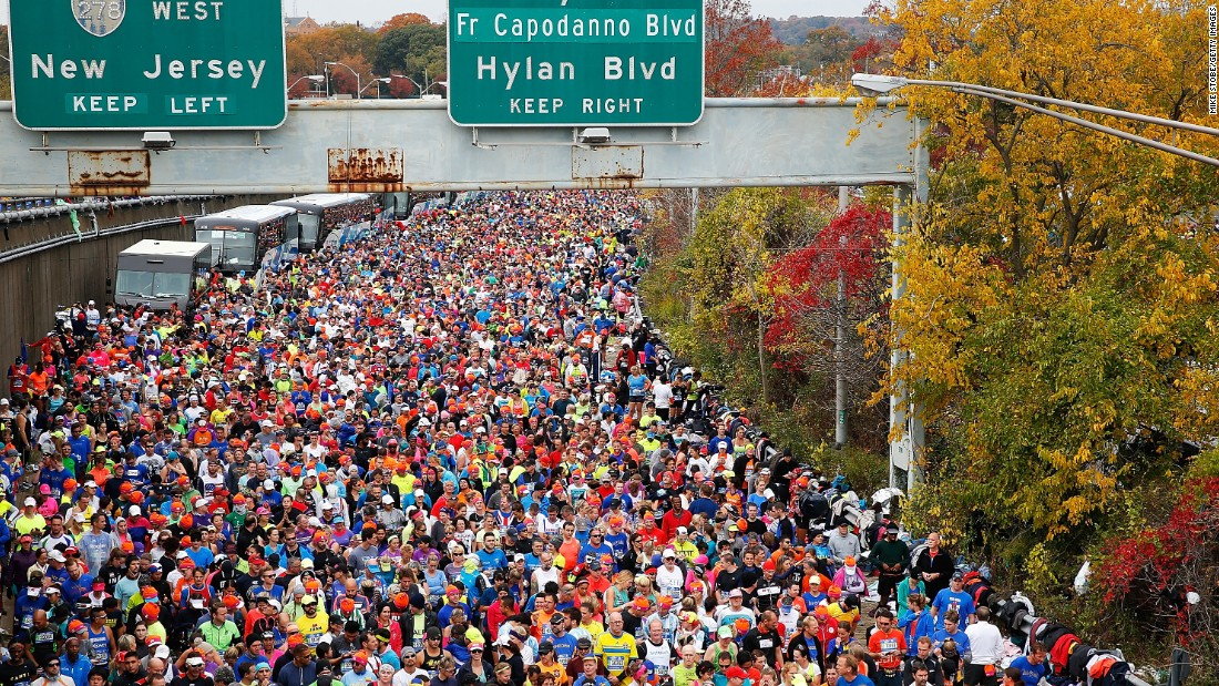 "Runners wait at <a href=""http://bleacherreport.com/articles/2584896-new-york-marathon-results-2015-mens-and-womens-top-finishers?utm_source=cnn.com&utm_medium=referral&utm_campaign=editorial"" target=""_blank"">the starting line</a> prior to crossing the Verrazano-Narrows Bridge."