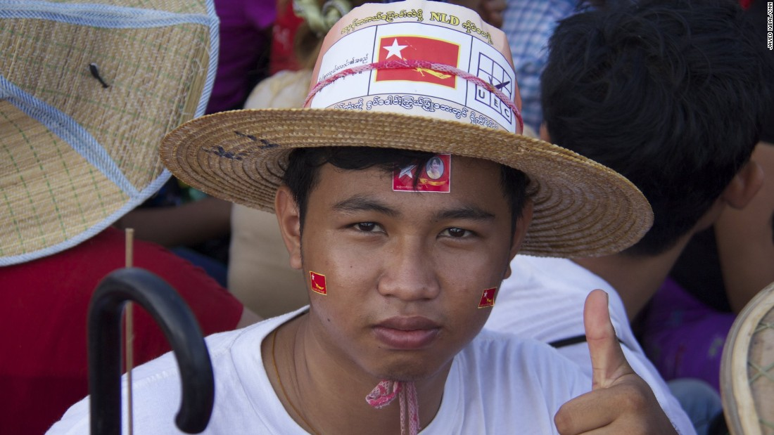 An NLD supporter dons accessories at the rally on November 1. The scene is festive because it's the first time in a generation party supporters get the chance to vote in national elections.