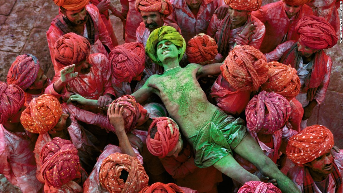 """McCurry has made many of these holy treks himself, and the rich tapestry of India's different faiths is one of the enduring themes of his work,"" continues Dalrymple.<br /><br />""There are beautiful images of devotees immersing statues of Ganesh in the sea at Mumbai, or playing Holi, the festival of colors, in Rajasthan, or visiting astrologers on the ghats of Varanasi.""<br /><br />This luminously-colored photograph shows the crowd carrying a man during the Holi Festival in Rajasthan, in 1996."