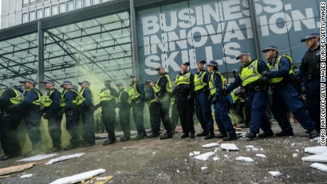LONDON, ENGLAND - NOVEMBER 04:  Police are pelted with missiles and smoke grenades at the Department for Business, Innovation and Skills during a demonstration against education cuts on November 4, 2015 in London, England. University students from across the country are marching on the streets of London to protest against cuts to free education. After a rally outside what was the University of London Union, the march will take in Parliament Square, Milibank - occupied by student protesters five years ago - and end in front of the Department for Business, Innovation and Skills (the department responsible for universities).  (Photo by Chris Ratcliffe/Getty Images)