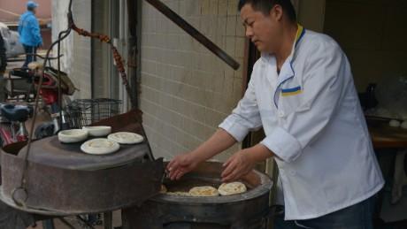 Wangkui Roujiamo restaurant's Liu Lianpeng bakes mo on a traditional furnace.