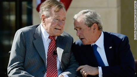 Former President George W. Bush (R) talks to his father President George H.W. Bush during the opening ceremony of the George W. Bush Presidential Center April 25, 2013 in Dallas, Texas.