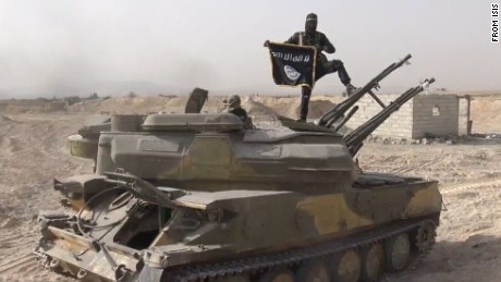 In this image taken from social media, an ISIS fighter holds the group's flag as he stands on a tank, purportedly captured when they took over the town of Qaryatain, Syria.