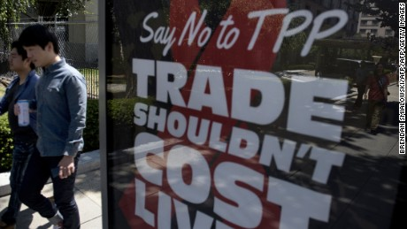 People pass an advertisement protesting the passage of the Trans-Pacific Partnership in Washington, DC on July 23, 2015. Expectations that the Trans-Pacific Partnership (TPP), an accord that would encompass 40 percent of global trade, would be sealed this year increased after US President Barack Obama was last month given fast-track authority by Congress to negotiate such deals. AFP PHOTO/BRENDAN SMIALOWSKI        (Photo credit should read BRENDAN SMIALOWSKI/AFP/Getty Images)