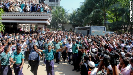 People gather outside a court as police escort the accused in the killing of Samiul Islam Rajon before a verdict in Sylhet, Bangladesh, on November 8, 2015.