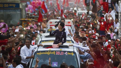 Myanmar opposition leader Aung San Suu Kyi gestures towards supporters as she travels in a motorcade ahead of a campaign rally for the National League for Democracy in Yangon on November 1, 2015. Myanmar heads to the polls on November 8 in what observers and voters hope will be the fairest election in decades as the nation slowly shakes off years of brutal and isolating junta rule.  AFP PHOTO / Ye Aung THU        (Photo credit should read Ye Aung Thu/AFP/Getty Images)