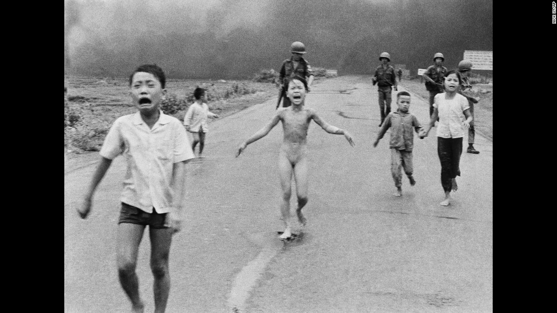 "<a href=""http://www.cnn.com/2015/06/22/world/kim-phuc-where-is-she-now/"" target=""_blank"">Nine-year-old Kim Phuc</a>, center, runs with her brothers and cousins, followed by South Vietnamese forces, down Route 1 near Trang Bang after a South Vietnamese plane accidentally dropped flaming napalm on its own troops and civilians on June 8, 1972. The terrified girl had ripped off her burning clothes while fleeing. Associated Press photographer Nick Ut used a Leica with a 35mm lens. The film was Kodak Tri-X.  Shutter speed and aperture are unknown. The photo was honored with a Pulitzer Prize in 1973."