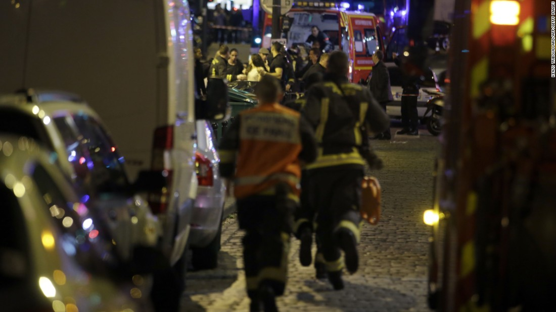 French security forces rush in as people are evacuated in the area of Rue Bichat in the 10th District of Paris.
