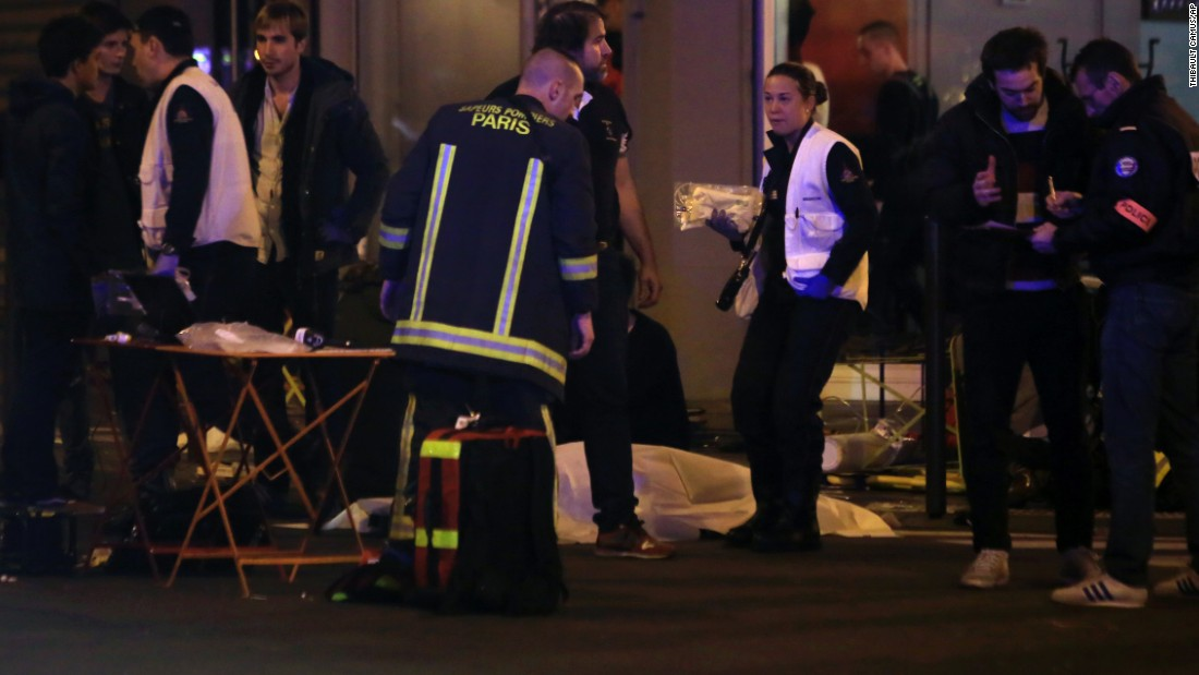 Rescue workers and medics tend to victims at the scene of one of the shootings, a restaurant in the 10th District. Attackers reportedly used AK-47 automatic weapons in separate attacks across Paris, and there were explosions at the Stade de France.