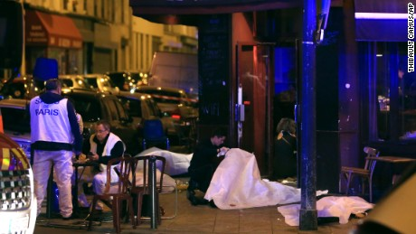 Victims lay on the pavement in a Paris restaurant, Friday, Nov. 13, 2015. Police officials in France on Friday reported a shootout in a Paris restaurant and an explosion in a bar near a Paris stadium. It was unclear if the events were linked. (AP Photo/Thibault Camus)
