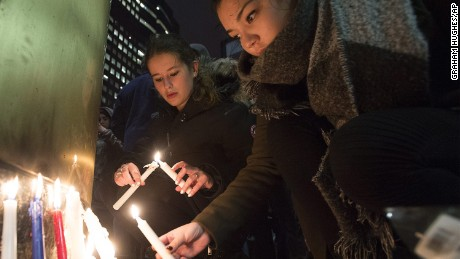 "People light candles at a vigil outside the French consulate in Montreal, Friday, Nov. 13, 2015. Canadian Prime Minister Justin Trudeau offered ""all of Canada's support"" to France on Friday night in the wake of ""deeply worrying"" terrorist attacks in Paris. (Graham Hughes/The Canadian Press via AP)"