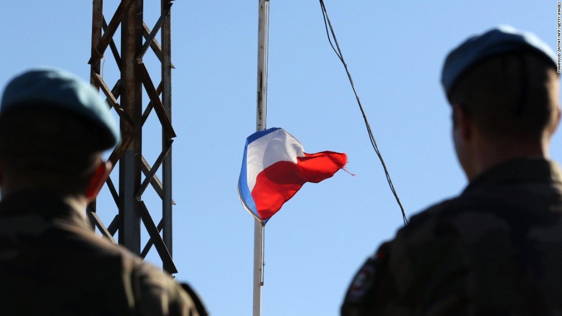 French soldiers of the United Nations' interim forces in Lebanon observe the national flag at half-staff at the contingent headquarters in the village of Deir Kifa on November 14.