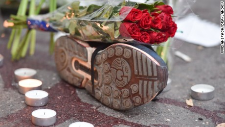 Image #: 40824580    Red roses on a sports shoe, next to a trail of blood, outside the Bataclan music club in Paris, France, 14 November 2015. At least 120 people have been killed in a series of terrorist attacks in Paris. PHOTO: UWE ANSPACH/DPA     DPA /LANDOV
