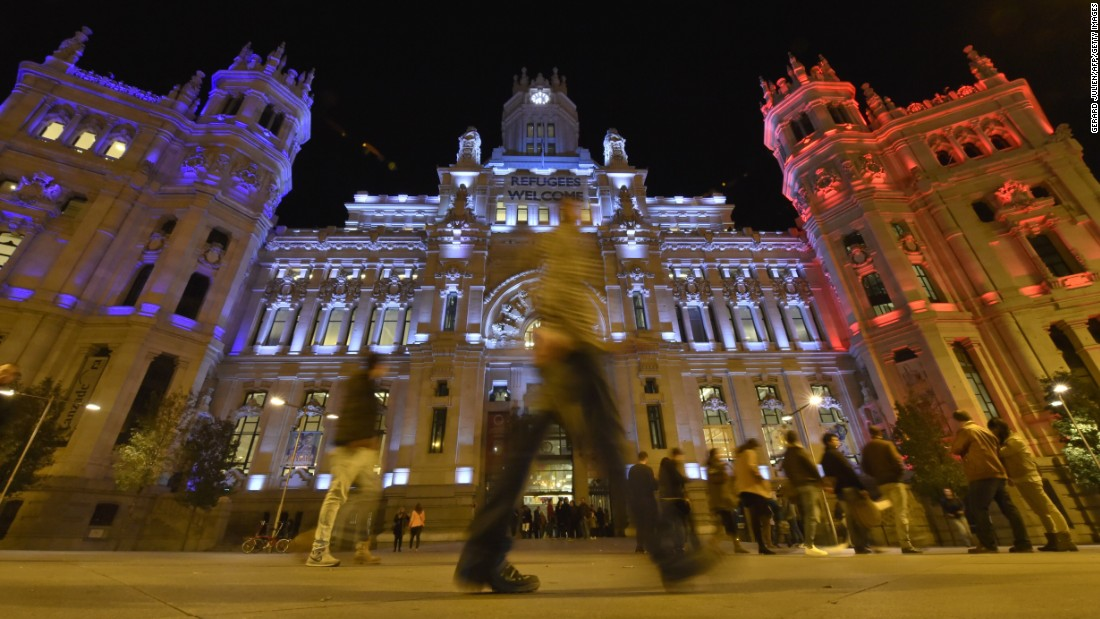People cross the street past the Cibeles Palace, Madrid's town hall, on November 14.