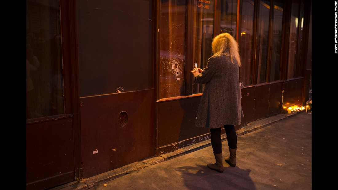 A woman takes a picture of a window shattered by bullets on November 14.