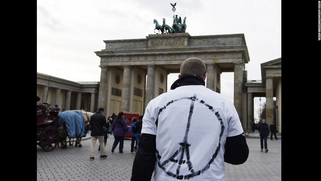 A man wears a shirt with a sign combining a peace symbol with the Eiffel tower in front of the Brandenburg Gate near the French embassy in Berlin.