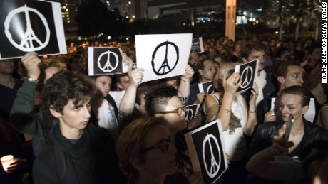 HONG KONG - NOVEMBER 14:  People hold peace signs as they gather during a memorial event for victims of the Paris terror attacks on November 14, 2015 in Hong Kong, Hong Kong. At least 120 people have been killed and over 200 injured, 80 of which seriously, following a series of terrorist attacks in the French capital.  (Photo by Xaume Olleros/Getty Images)