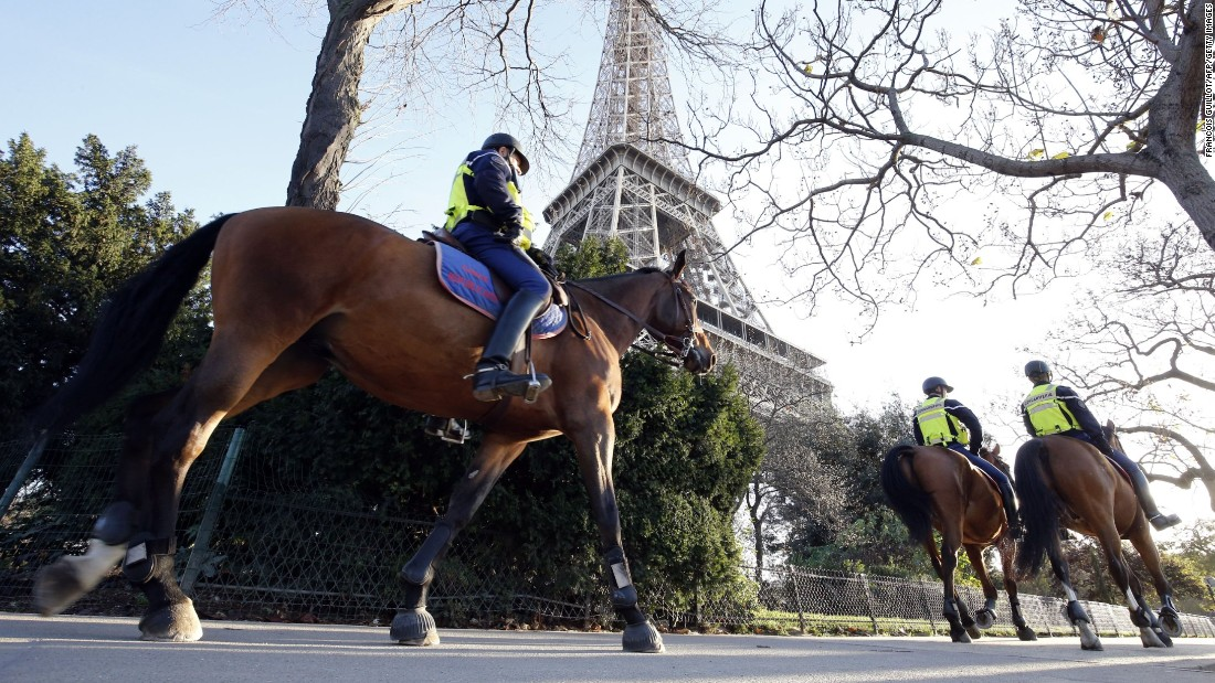 Mounted police officers patrol in front of the Eiffel Tower in Paris on November 15.