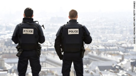 Police officers overlook Paris as they patrol in front of the Sacre Coeur Basilica on November 16, three days after a series of coordinated attacks claimed by Islamic State jihadists, which killed at least 129 people and left more than 350 injured.