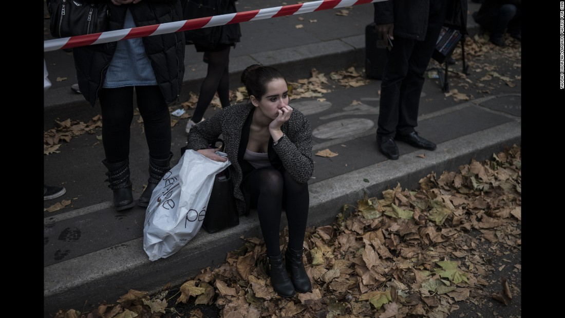 A woman on November 16 sits in front of the Parisian concert venue Balaclan, where many of the victims from the Paris attacks were killed.