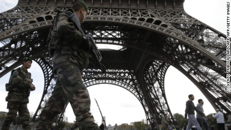 Soldiers patrol at the foot of the Eiffel Tower in Paris on November 16, 2015 three days after the terrorist attacks that left at least 129 dead and more than 350 injured. France prepared to fall silent at noon on November 16 to mourn victims of the Paris attacks after its warplanes pounded the Syrian stronghold of Islamic State, the jihadist group that has claimed responsibility for the slaughter. AFP PHOTO / KENZO TRIBOUILLARD        (Photo credit should read KENZO TRIBOUILLARD/AFP/Getty Images)