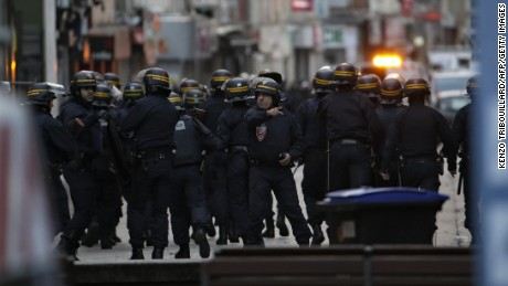 Policemen take combat position in Saint-Denis city center, northern Paris on Wednesday as French Police special forces raid an apartment targeting suspects in last week's terrorist attacks.