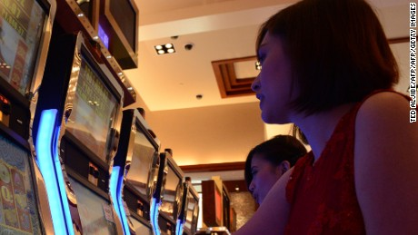 Employees of Solaire Manila Resorts and casino pose for photo next to gaming machines inside the casino in Manila on March 14, 2013, ahead of its opening on March 16.  The Philippines makes its biggest bet this weekend in a high-stakes bid to join the world's elite gaming destinations, with the launch of a $1.2-billion casino on Manila Bay.Solaire Manila Resorts is the first of four enormous entertainment venues slated to rise over a giant chunk of prime, reclaimed land that industry and government leaders expect will attract millions of cashed-up Asian tourists.    AFP PHOTO/TED ALJIBE        (Photo credit should read TED ALJIBE/AFP/Getty Images)