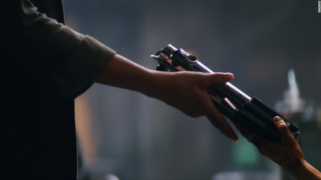 "This shot from the official trailer shows a lightsaber changing hands, while Luke Skywalker, talking about the Force, says, ""My sister has it."" The lightsaber in question looks like Anakin's, which Luke inherits in Episode IV. So who's getting it? Well, we think they're female hands. Is that Leia gaining custody of her brother's weapon? Or is she passing it on to Rey? Are there any other female characters around that we haven't seen yet?"