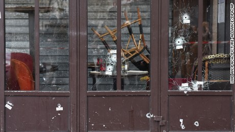 Bullet holes in the Café Bonne Bière storefront are a reminder of the carnage.