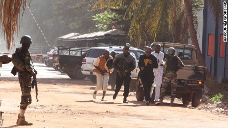 Peopel flee the Radisson Blu Hotel in Bamako, Mali, on Friday, November 20. Gunmen have stormed the hotel and taken 170 hostages with at least three deaths reported.