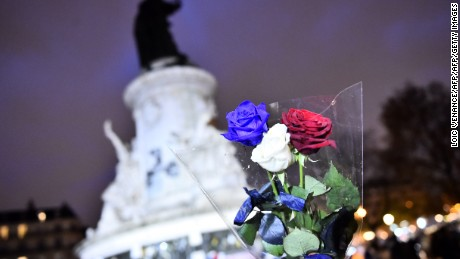A man holds roses in the colours of the French national flag at Place de la Republique (Republic Square) in Paris on November 21, 2015 as he arrives to pay tribute to the victims of the November 13 terror attacks. A coordinated wave of attacks on Parisian nightspots claimed by Islamic State group (IS) jihadists killed 130 people.  AFP PHOTO / LOIC VENANCE        (Photo credit should read LOIC VENANCE/AFP/Getty Images)
