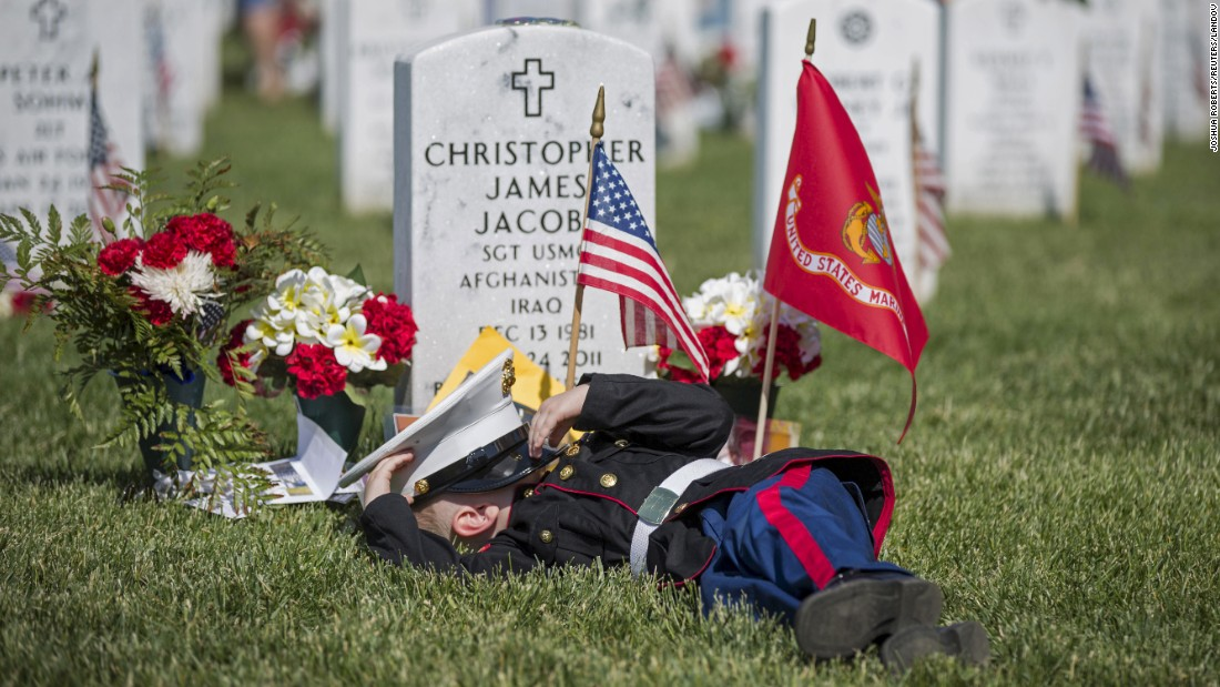 "<strong>May 25:</strong> Christian Jacobs, 4, lies on the grave of his father, Christopher James Jacobs, during a <a href=""http://www.cnn.com/2015/05/23/us/gallery/memorial-day-2015/index.html"" target=""_blank"">Memorial Day</a> event at Arlington National Cemetery in Virginia."