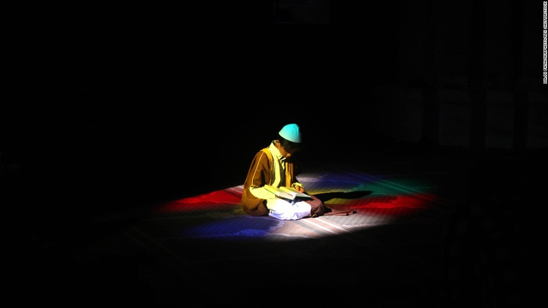<strong>June 19:</strong> During the holy month of Ramadan, a Palestinian boy reads the Quran at a mosque in Gaza City.