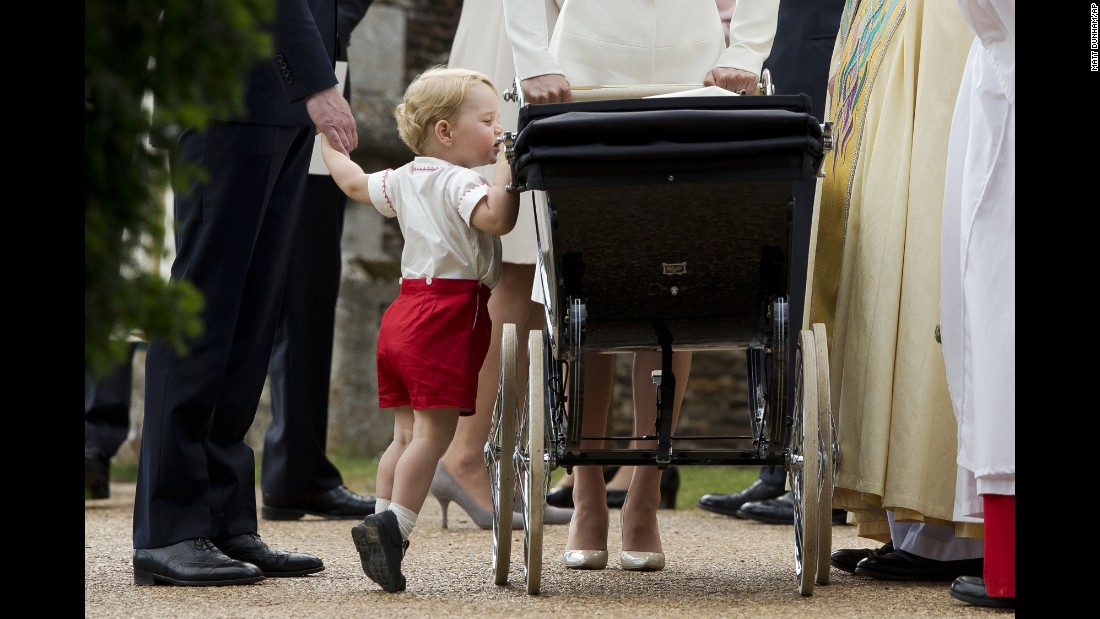 "<strong>July 5:</strong> Britain's Prince George peeks into the carriage holding his sister, Princess Charlotte, <a href=""http://www.cnn.com/2015/05/02/world/gallery/royal-baby-princess-announced/index.html"" target=""_blank"">after her christening</a> in Norfolk, England."