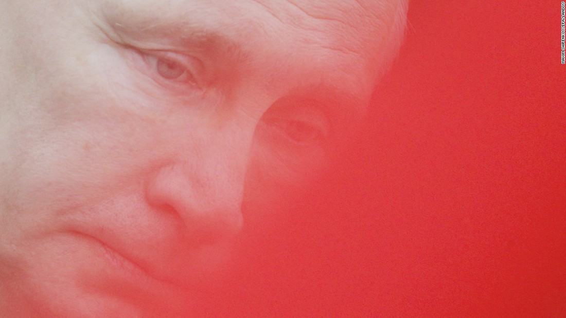 <strong>February 23: </strong>Russian President Vladimir Putin, seen through a red flag, attends a wreath-laying ceremony in Moscow on Defender of the Fatherland Day.