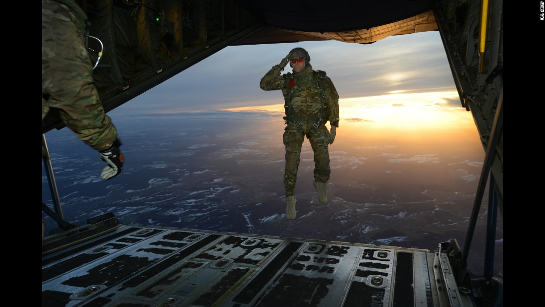 <strong>February 24:</strong> A U.S. soldier salutes while jumping out of an aircraft in Germany.