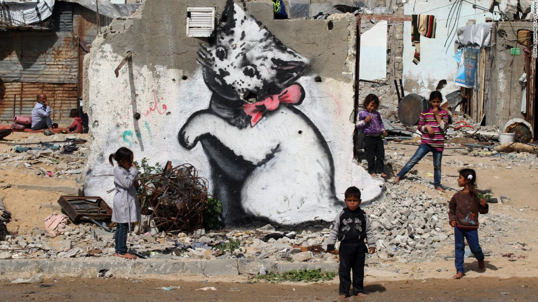 "<strong>February 26:</strong> Children stand next to a Banksy mural on the remains of a destroyed house in Beit Hanoun, Gaza. The house was destroyed last year during fighting between Israel and Hamas.<a href=""http://www.cnn.com/2013/10/14/living/gallery/banksy-street-artist/index.html"" target=""_blank""> See more work from Banksy, the anonymous street artist</a>"